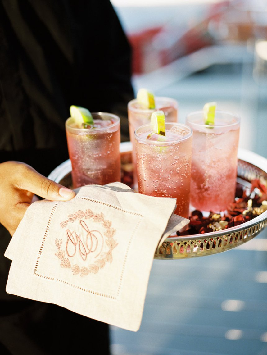 monogram cocktail napkin and cranberry specialty cocktail on tray