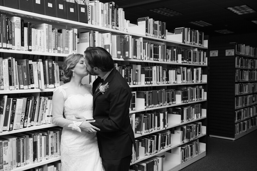 bride and groom kissing in library book shelves