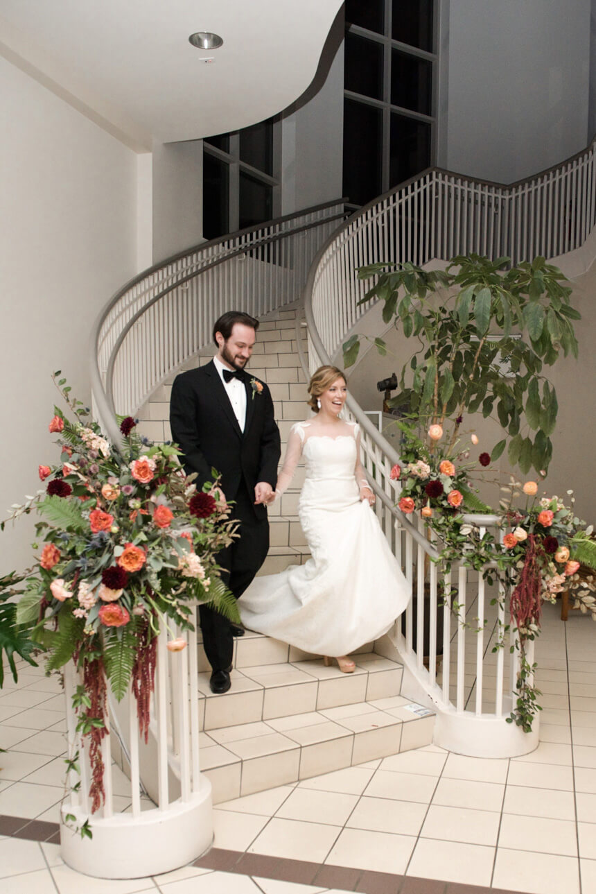 bride and groom at North Shelby library staircase wedding reception