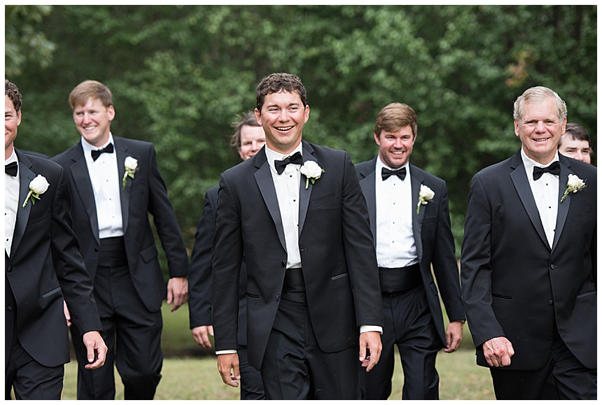 groomsmen in traditional black tuxes with bow ties