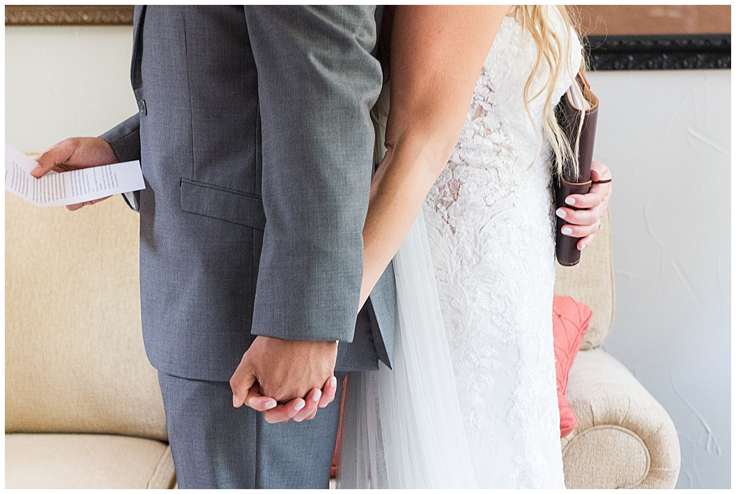 bride and groom back to back holding hands first look