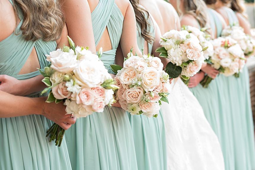 pastel wedding flowers held by bridesmaids in green dresses